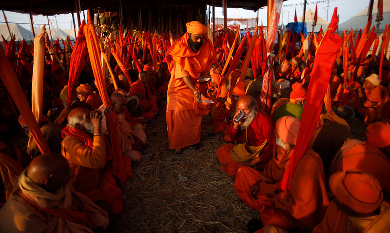 ". A Hindu holy man distributes money as part of charity to ""ekadandi\"", or single staff holding sect of Hindu holy men, during the Maha Kumbh festival in Allahabad, India, Monday, Jan. 28, 2013. Millions of Hindu pilgrims are expected to attend the Maha Kumbh festival, which is one of the world\'s largest religious gatherings that lasts 55 days and falls every 12 years. The \""ekadandis\"" are an ancient sect of traveling renunciates belonging to the Vaishnavite sect. (AP Photo/Saurabh Das)"