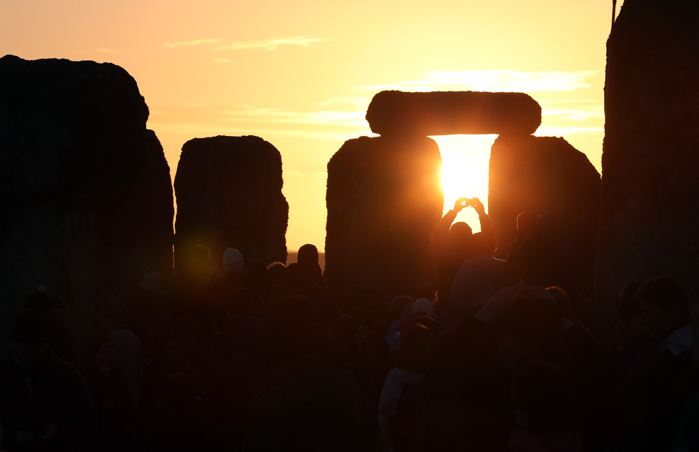 Description of . A man takes a photograph of the sunrise as druids, pagans and revellers celebrate the winter solstice at Stonehenge on December 21, 2012 in Wiltshire, England. Predictions that the world will end today as it marks the end of a 5,125-year-long cycle in the ancient Maya calendar, encouraged a larger than normal crowd to gather at the famous historic stone circle to celebrate the sunrise closest to the Winter Solstice, the shortest day of the year.  (Photo by Matt Cardy/Getty Images)