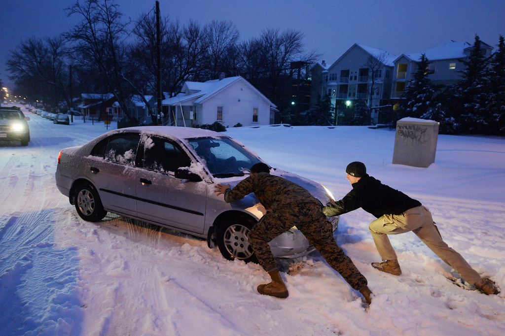 . People help push a car stuck in the snow during a snowstorm in Alexandria, Virginia, USA, 13 February 2014. The Washington DC area was pounded by a snowstorm, with accumulation expected to reach twelve inches in some areas, as the storm moved up the mid-Atlantic to the Northeast region of the US.  EPA/MICHAEL REYNOLDS  EPA/