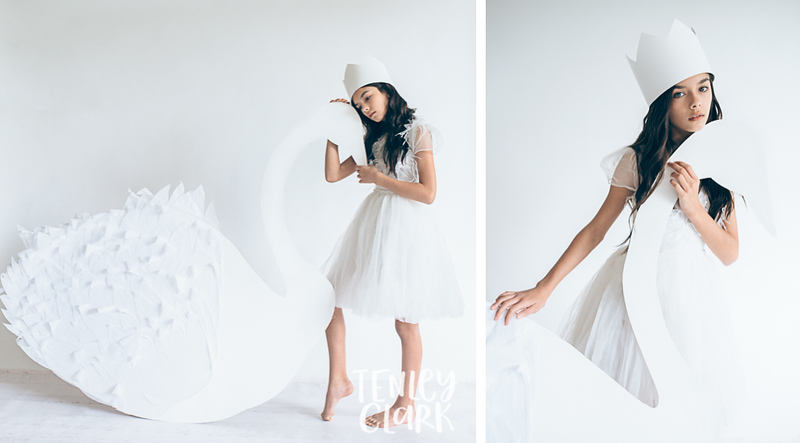 Girl with paper crown and giant paper swan. Whimsical kid's fashion editorial with giant white paper origami props. Photography by Tenley Clark.