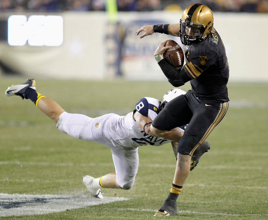 . Army quarterback Trent Steelman (R) is tackled after rushing for a gain by Navy defender Wave Ryder (8) during the third quarter of the Army versus Navy NCAA football game in Philadelphia, Pennsylvania, December 8, 2012. REUTERS/Tim Shaffer