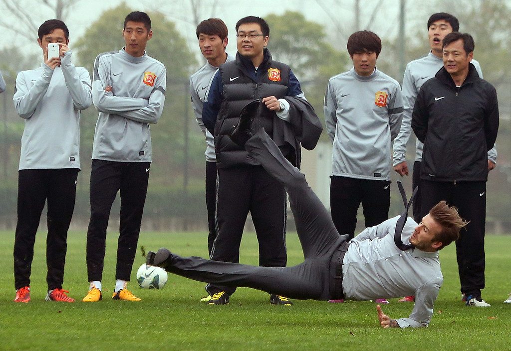 . Soccer superstar David Beckham falls down after illustrating how to take a free kick during a visit to the Zall Football Club in Wuhan, central China\'s Wuhan province on March 23, 2013. Beckham raised the prospect of one last stop on his global football journey on March 20, refusing to rule out playing in China after his contract with Paris Saint-Germain ends. STR/AFP/Getty Images