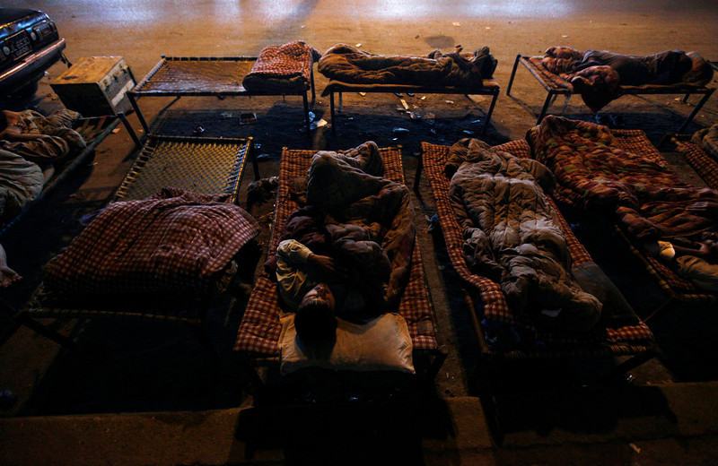 . Men sleep on charpoy beds along a road nearby a railway station in Karachi March 31, 2013. Charpoy bed guesthouses are only set up at night from 9pm to 7am for the homeless, passengers and drivers, charging about 40 Pakistani rupees ($0.40) per night. Picture taken March 31, 2013. REUTERS/Akhtar Soomro