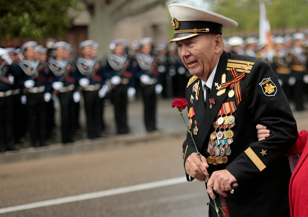 . A WWII veteran holds a flower during a Victory Day military parade in Sevastopol, Crimea, Friday, May 9, 2014. Crimea, which hosts a major Russian Black Sea Fleet base, is also set to hold a massive navy parade in the port of Sevastopol, celebrating the Russian takeover. (AP Photo/Ivan Sekretarev)