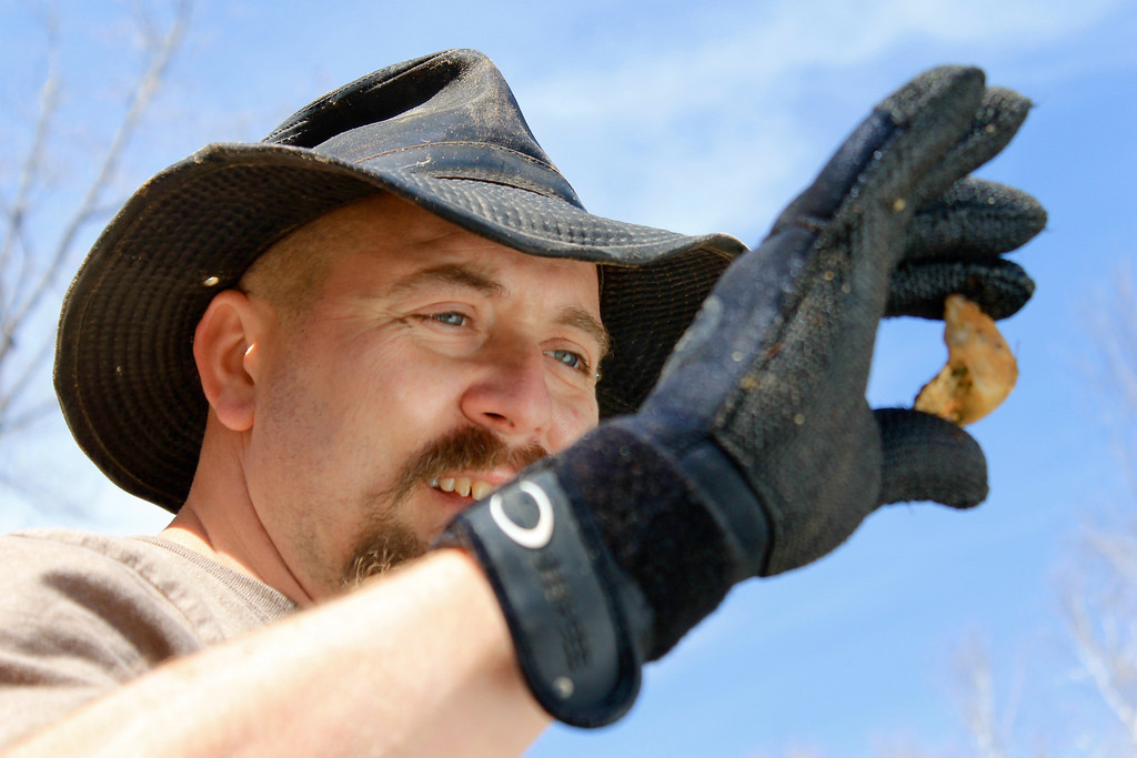 . Chad Watkins checking out a rock. Ezra Wolfinger/Discovery Communications