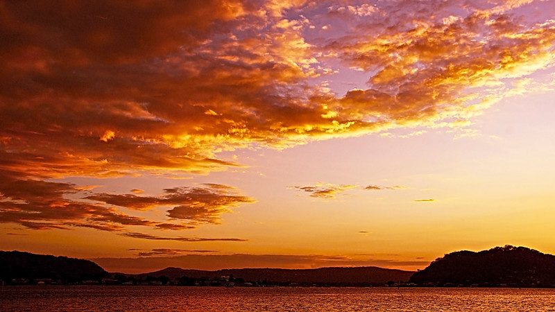 Orange coloured Stratocumulus cloud, sunset seascape.