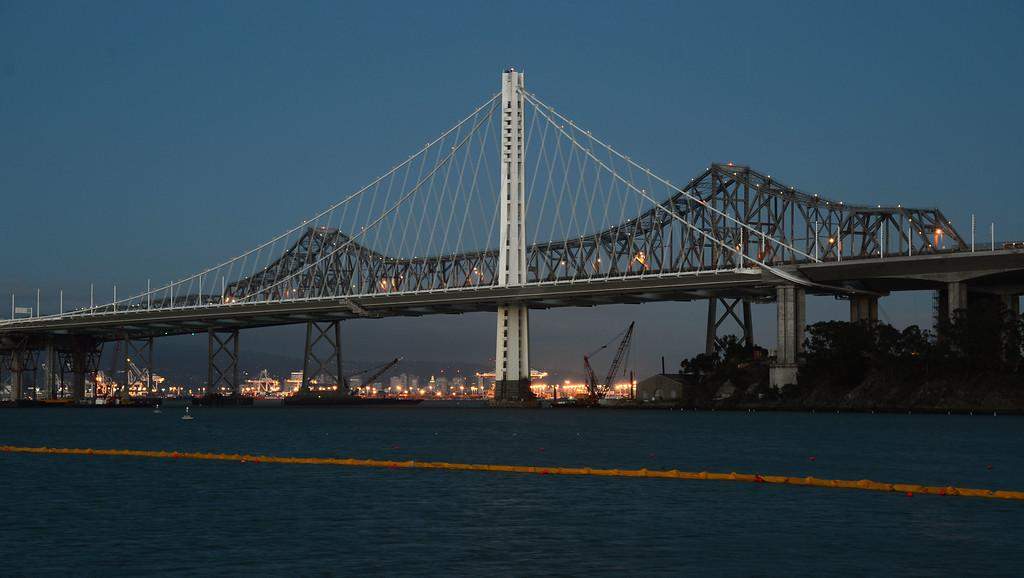 . One week before the cantilever section of the old Bay Bridge is officially closed, the new eastern span of the Bay Bridge, and its 525-foot tall iconic tower, glow in the dusk light Wednesday evening Aug. 21, 2013.  (Karl Mondon/Bay Area News Group)