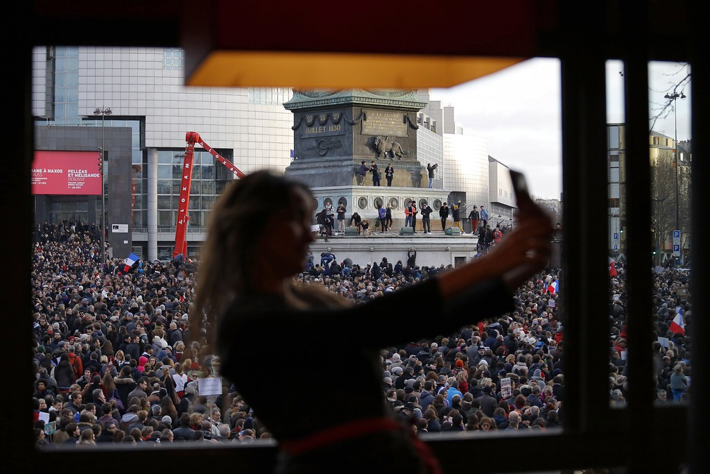 . A woman takes a selfie as the crowd gathers on Bastille square, in Paris, France, Sunday, Jan. 11, 2015. Hundreds of thousands of people marched through Paris on Sunday in a massive show of unity and defiance in the face of terrorism that killed 17 people in France\'s bleakest moment in half a century. (AP Photo/Laurent Cipriani)