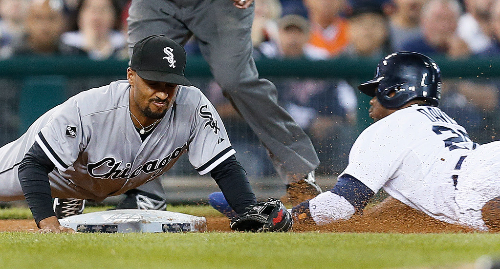 . Detroit Tigers left fielder Rajai Davis, right, steals third base as Chicago White Sox third baseman Marcus Semien can\'t handle the throw in the fifth inning of a baseball game in Detroit Tuesday, Sept. 23, 2014. Davis scored on the overthrow. (AP Photo/Paul Sancya)