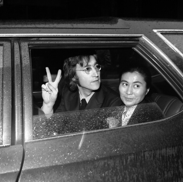 . Former Beatle John Lennon, left, and his wife Yoko Ono, leave the Immigration and Naturalization Service, at 20 West Broadway, March 16, 1972, New York. His case was postponed and comes up in April (AP Photo/Anthony Camerano)