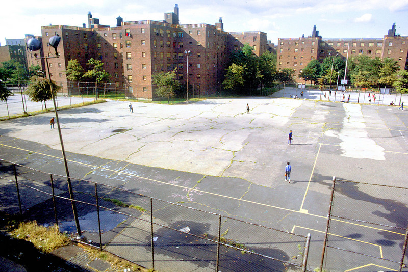 Kids are playing baseball in the foreground and basketball in the background in the upper right.