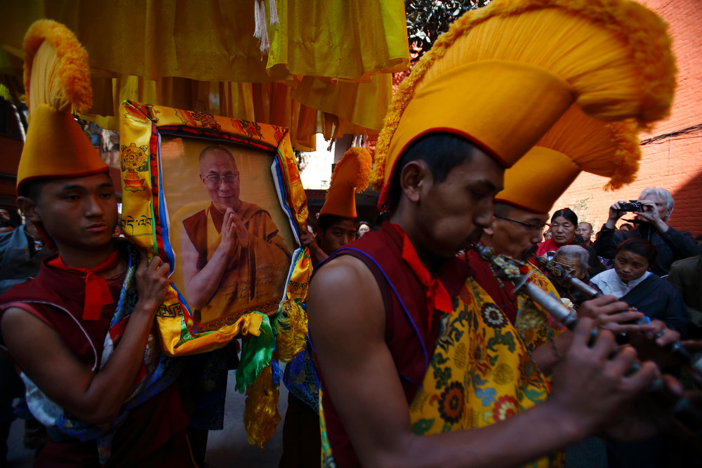 Description of . Tibetan monks carry a portrait of their spiritual leader Dalai Lama while performing rituals during a function organized at the Tibetan monastery in Boudhanath Stupa to mark the third day of New Year or