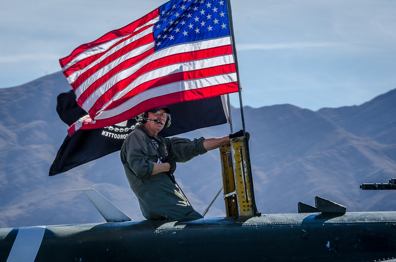 Airman on B-25 Mitchell flying the U.S. and MIA Flags