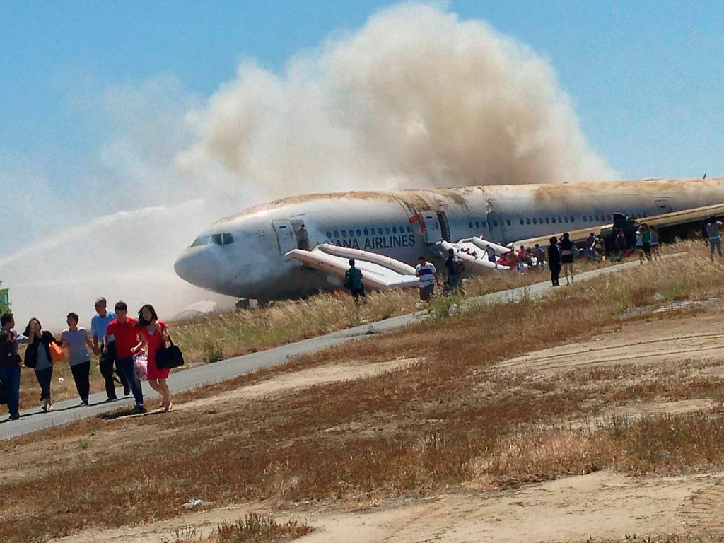 . Passengers evacuate the Asiana Airlines Boeing 777 aircraft after a crash landing at San Francisco International Airport in California on July 6, 2013 in this photo provided by passenger Eugene Anthony Rah released to Reuters on July 8, 2013.  REUTERS/Eugene Anthony Rah/Handout via Reuters