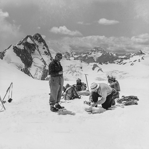 1955 Fr Doherty, John McWilliams (on stove), Bill Toomey and JER Mathews (photographer) at  Lunch on Tasman Saddle 2 (LF trans) a.jpg