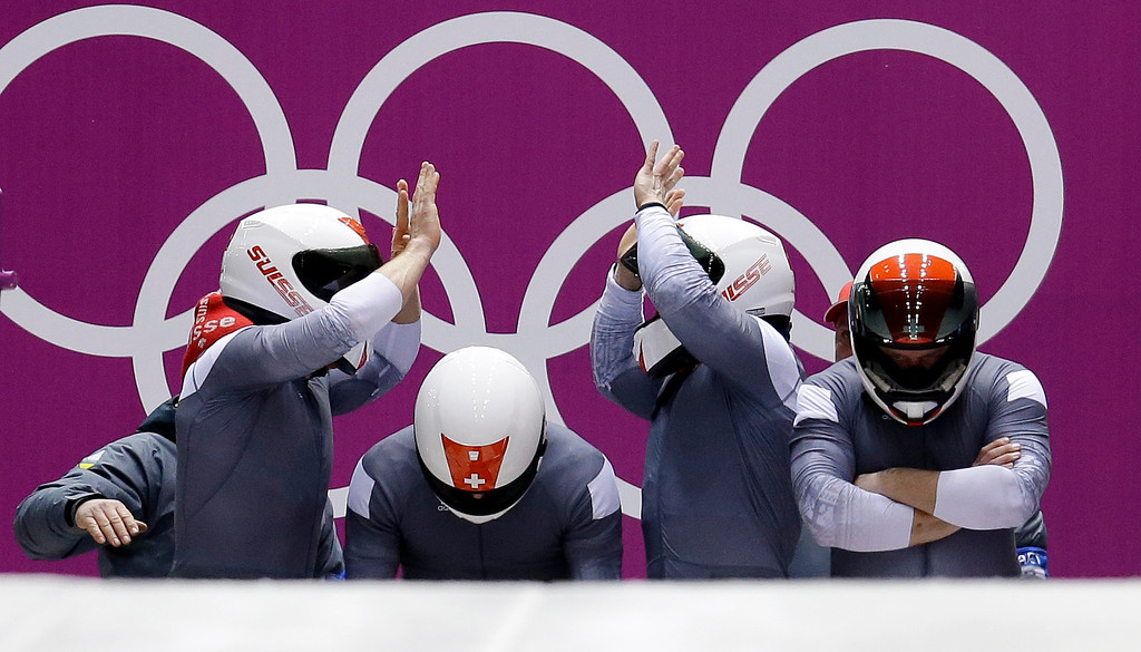 . The team from Switzerland SUI-1, with Beat Hefti, Alex Baumann, Juerg Egger and Thomas Lamparter, start their first run during the men\'s four-man bobsled competition at the 2014 Winter Olympics, Saturday, Feb. 22, 2014, in Krasnaya Polyana, Russia. (AP Photo/Natacha Pisarenko)