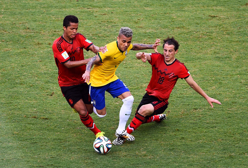 . FORTALEZA, BRAZIL - JUNE 17: Dani Alves of Brazil is challenged by Giovani dos Santos (L) and Andres Guardado of Mexico during the 2014 FIFA World Cup Brazil Group A match between Brazil and Mexico at Castelao on June 17, 2014 in Fortaleza, Brazil.  (Photo by Jamie McDonald/Getty Images)