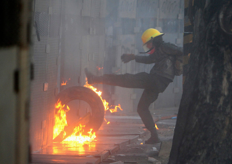 . A protester kicks a burning tyre against a barricade set up around congress during a protest against Mexico\'s new President Enrique Pena Nieto, outside congress in Mexico City December 1, 2012. Pena Nieto took over as Mexican president on Saturday, offering a shot at redemption for the party that shaped modern Mexico if he can bring about an end to years of violence and economic underperformance. REUTERS/Ginnette Riquelme