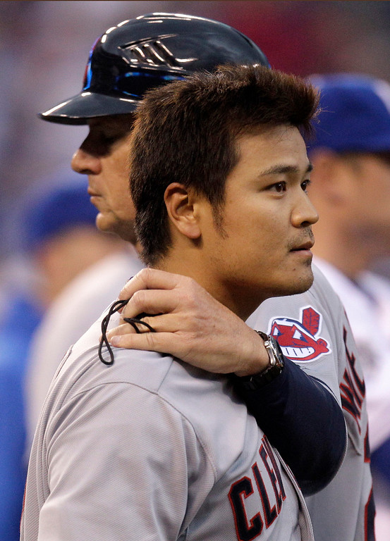. Cleveland Indians\' Shin-Soo Choo is held back by first base coach Tom Wiedenbauer after a brawl erupted when Choo was hit by a pitch thrown by Kansas City Royals starting pitcher Jonathan Sanchez during the third inning of a baseball game on Saturday, April 14, 2012, in Kansas City, Mo. (AP Photo/Charlie Riedel)