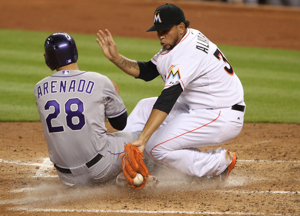 . Pitcher Henderson Alvarez #37 of the Miami Marlins cannot make the tag at home plate against Nolan Areado #28 of the Colorado rockies during the fourth inning at Marlins Park on April 2, 2014 in Miami, Florida.  (Photo by Marc Serota/Getty Images)