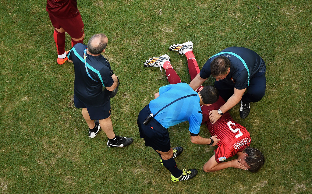 . An injured Fabio Coentrao of Portugal lies on the pitch as referee Milorad Mazic stands over during the 2014 FIFA World Cup Brazil Group G match between Germany and Portugal at Arena Fonte Nova on June 16, 2014 in Salvador, Brazil.  (Photo by Francois Xavier Marit - Pool/Getty Images)