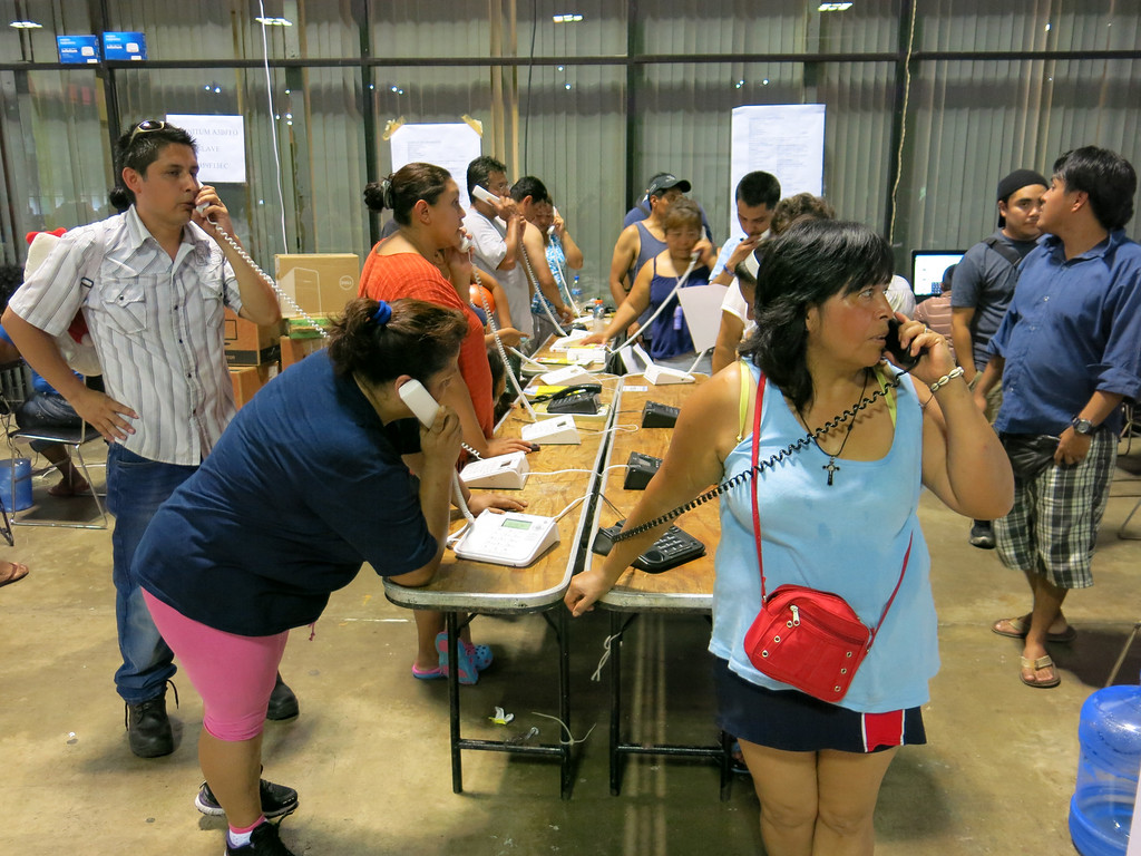 . Residents of the storm-battered southern Mexican state of Guerrero use the courtesy phones provided at a temporary shelter in the Convention Center in Acapulco, Mexico, Thursday, Sept. 19, 2013. Hundreds were in the shelter, including several hundred from a village hit by a landslide Monday afternoon, where officials said at least 58 people were missing and presumed dead. (AP Photo/Michael Weissenstein)
