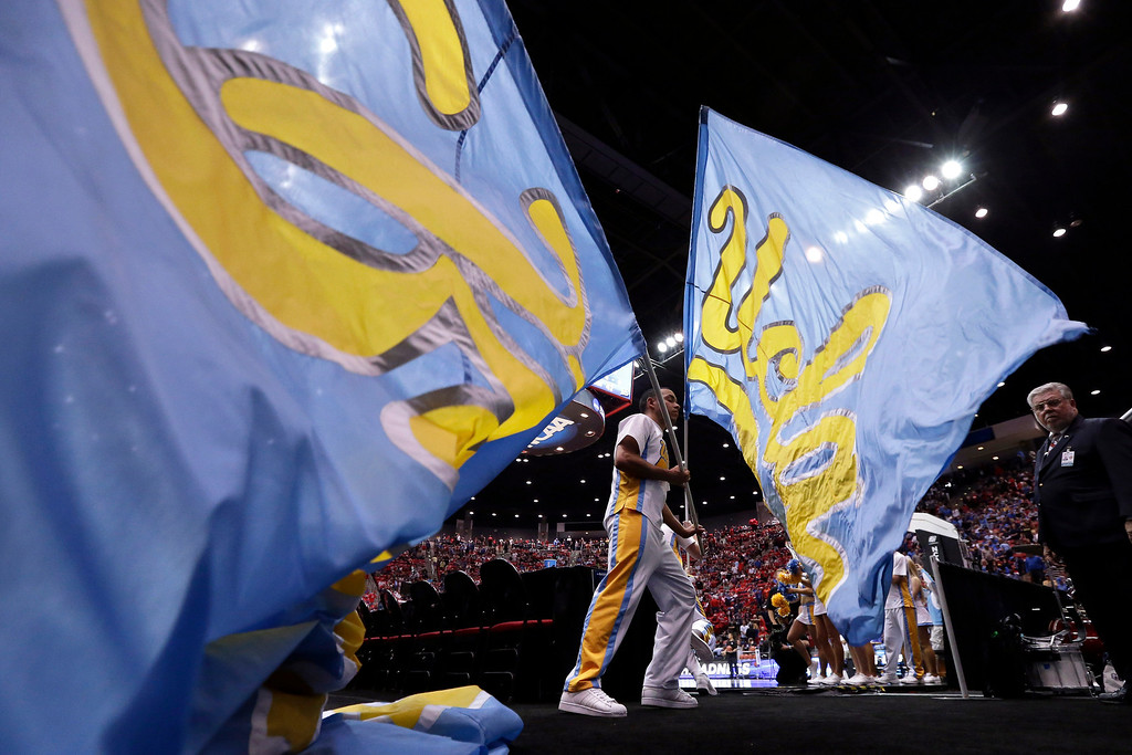 . A member of the UCLA drill team runs with a flag as the team takes the court for the second half against Stephen F. Austin during  a third-round game of the NCAA college basketball tournament, Sunday, March 23, 2014, in San Diego. UCLA won 77-60. (AP Photo/Gregory Bull)
