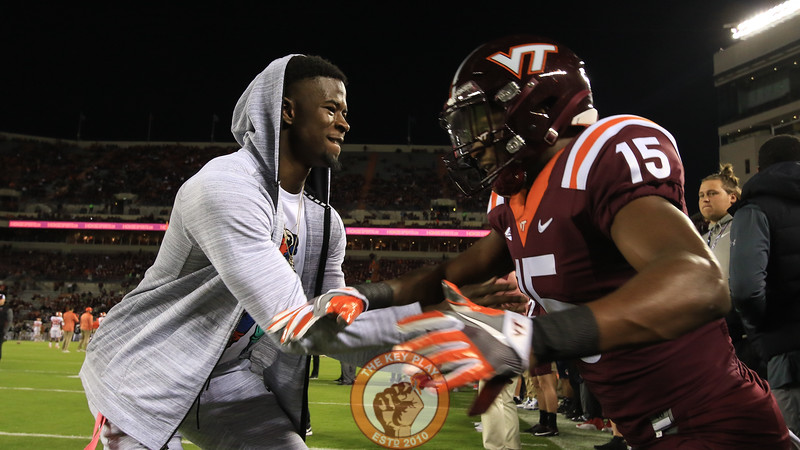 Former Virginia Tech and current NFL wide receiver Isiaiah Ford helps Sean Savoy warm up before the game. (Mark Umansky/TheKeyPlay.com)