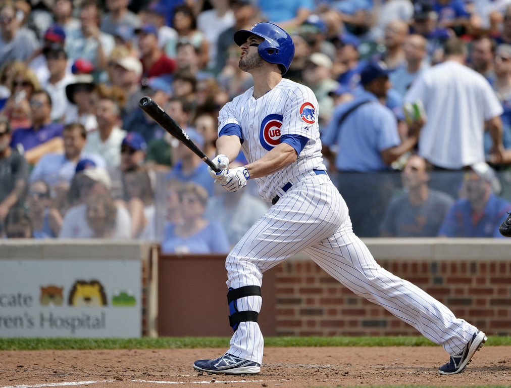 . Justin Ruggiano #20 of the Chicago Cubs follows through on a sacrifice fly scoring teammate Chris Coghlan during the sixth inning against the Colorado Rockies at Wrigley Field on July 31, 2014 in Chicago, Illinois.  (Photo by Brian Kersey/Getty Images)