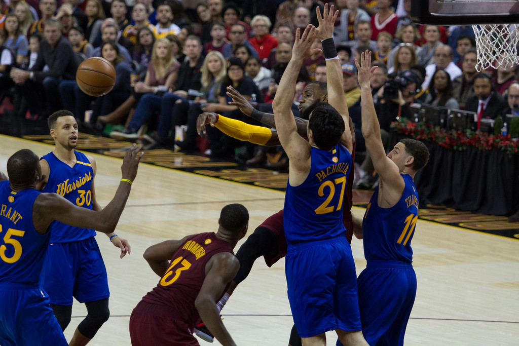 . LeBron James (23) of the Cleveland Cavaliers throws a pass in between Golden State Warrior defenders during an NBA game at the Quicken Loans Arena on Christmas day.  The Cavs defeated the Warriors 109-108.  Michael Johnson - The News Herald