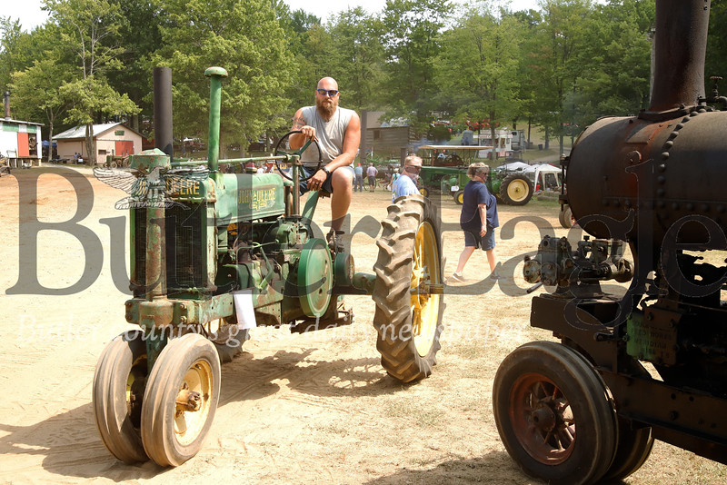 Jeremy Barnhart of Butler cruises past a steam engine at the Portersville Steam Show on his 1937 John Deere tractor Saturday. 08/03/19 Seb Foltz/Butler Eagle