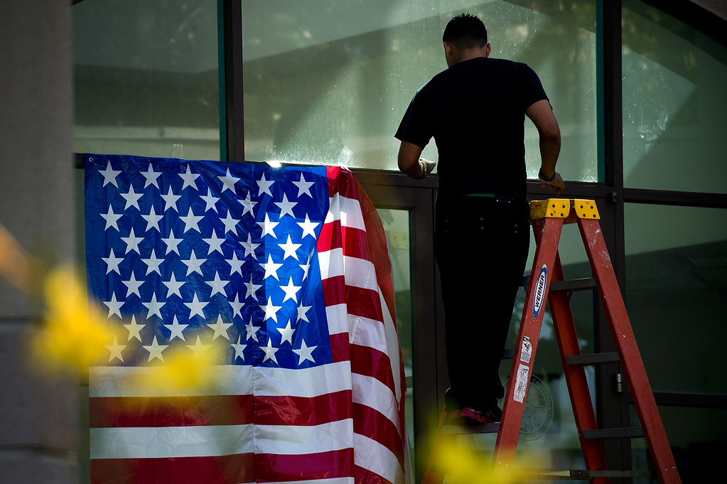 . A worker puts up an American flag in front of Palm Park Aquatic Center  during the 4th of July celbration in Whittier on Thursday, July 4, 2013. (SGVN/Staff photo by Watchara Phomicinda)