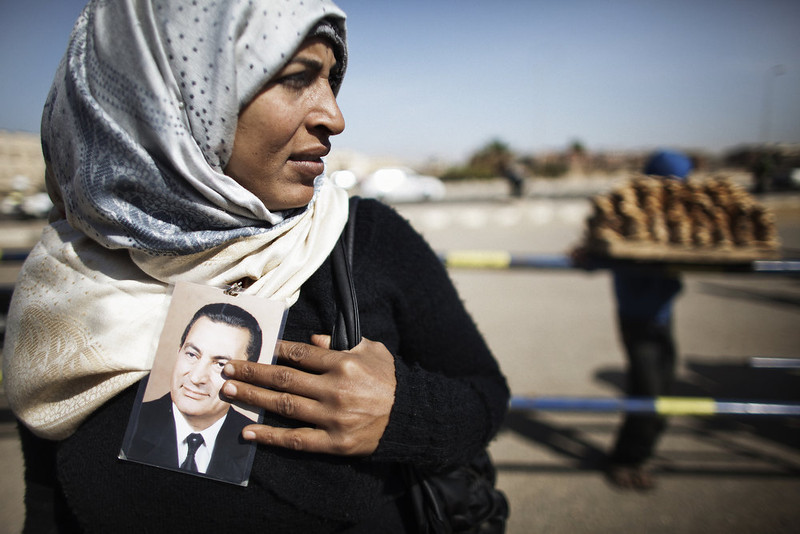 . A supporter of ousted Egyptian president Hosni Mubarak (portrait) waits for news from his trial outside the court in Cairo on February 22, 2012, as the landmark murder and corruption trial of the former leader entered its final day of hearings, with the judge expected to announce the date of the verdict. Cameras are not allowed inside the courtroom and state television did not show Mubarak or the defendants arriving in court.  MARCO LONGARI/AFP/Getty Images