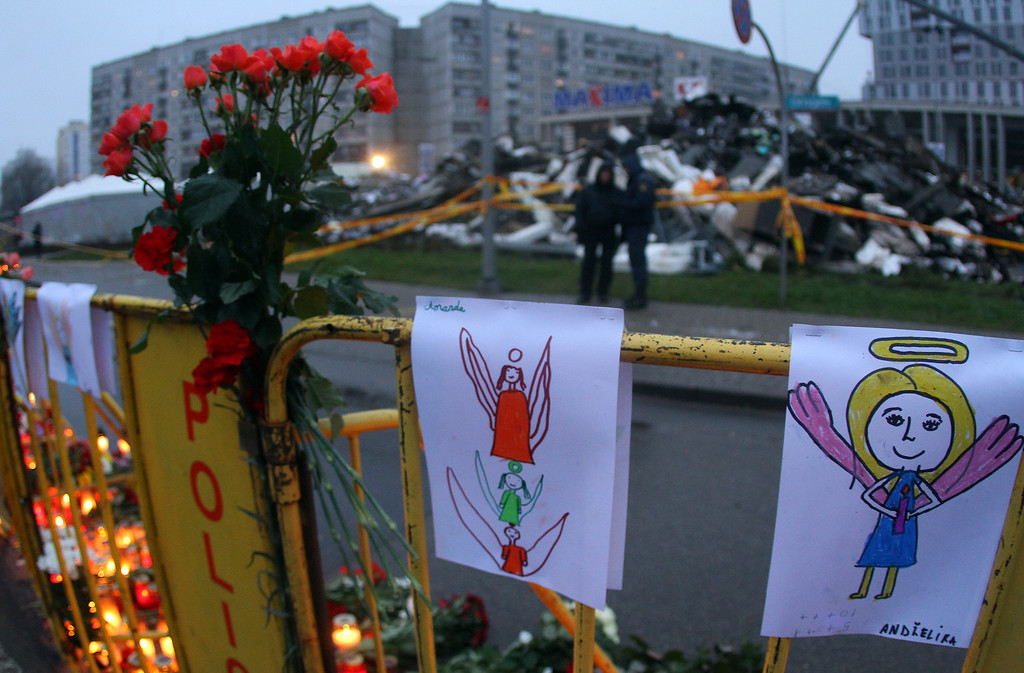 . Paintings and flowers are fixed on a fence near the accident site of a collapsed Maxima supermarket in Riga on November 23, 2013, where the roof of the building caved in on shoppers on November 21.    AFP PHOTO / PETRAS MALUKAS/AFP/Getty Images