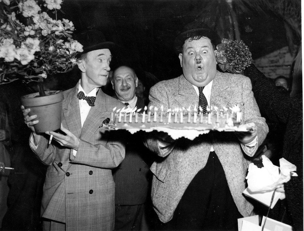 . Comedian Stan Laurel, left, looks on as Oliver Hardy gets ready to blow out the candles on his birthday cake in Billancourt, France, on Jan. 18, 1951.  Hardy is celebrating his 58th birthday.  The man at center is not identified.  (AP Photo)