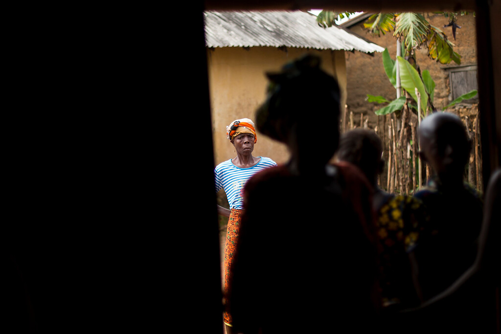 . In this photo taken Thursday Nov. 20, 2014, children listen to the village chief  in the communal room in the Guinean village of Meliandou, some 400 miles (600 mms) south-east of Conakry, Guinea, believed to be Ebola\'s ground zero.  (AP Photo/Jerome Delay)