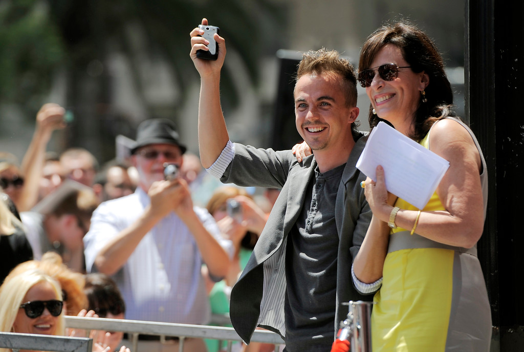""". Frankie Muniz, left, and Jane Kaczmarek, cast members in the television series \""""Malcolm in the Middle,\"""" wave to the crowd during a ceremony to award fellow cast member Bryan Cranston a star on the Hollywood Walk of Fame on Tuesday, July 16, 2013 in Los Angeles. (Photo by Chris Pizzello/Invision/AP)"""