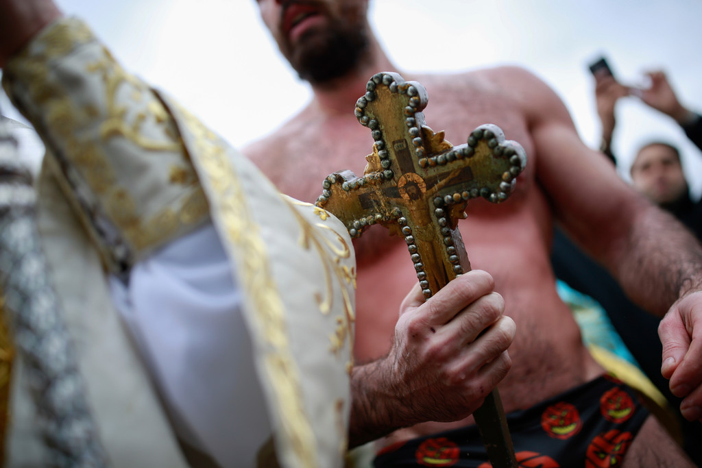 . Nicolaos Solis, 29, from Greece holds the wooden cross which was thrown into the waters by Ecumenical Patriarch Bartholomew I during the Epiphany ceremony to bless the waters at the Golden Horn in Istanbul, gets ashore, Friday, Jan. 6, 2017. (AP Photo/ Emrah Gurel)