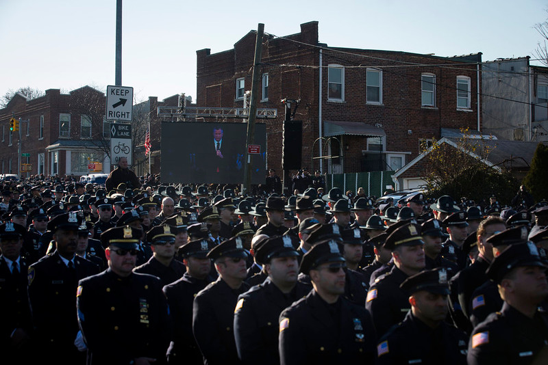 . Police officers turn their backs as New York City Mayor Bill de Blasio speaks at the funeral of New York city police officer Rafael Ramos in the Glendale section of Queens, Saturday, Dec. 27, 2014, in New York. Ramos and his partner, officer Wenjian Liu, were killed Dec. 20 as they sat in their patrol car on a Brooklyn street. The shooter, Ismaaiyl Brinsley, later killed himself. (AP Photo/John Minchillo)