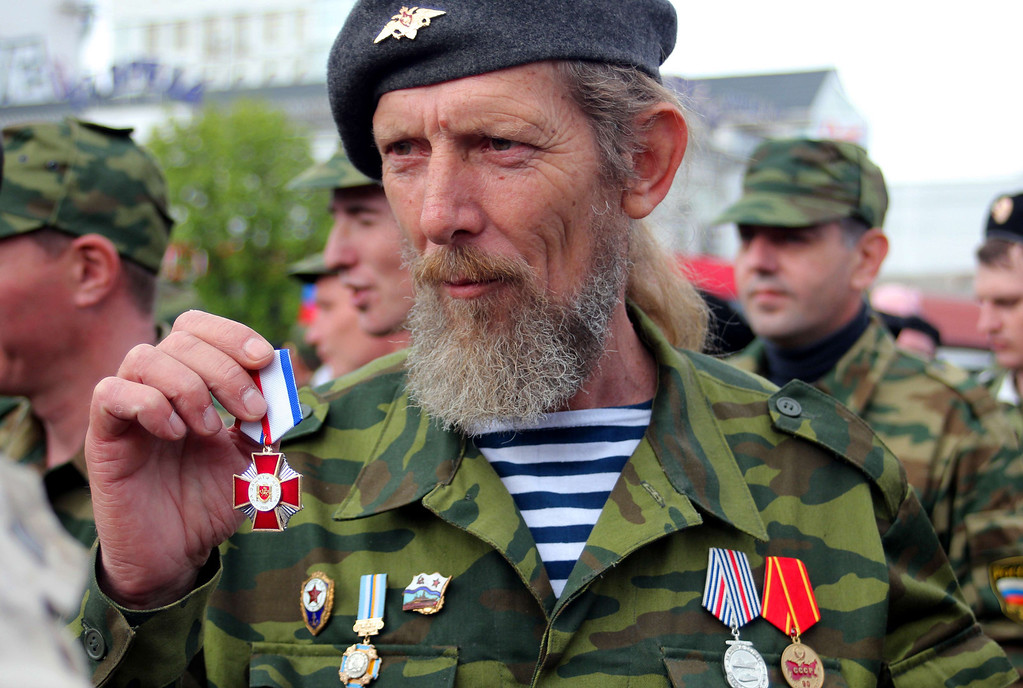 """. A member of pro-Russian self defense forces shows his medal \""""For the Defence of Crimea\"""" recently established by the local authorities in Simferopol on April 13, 2014, during in a ceremony to celebrate the 70th anniversary of the peninsula\'s capital Simferopol liberation from Nazi Germany troops during the World War II. Crimea\'s largely Russian-speaking residents voted in March to become part of Russia, in a hastily organised referendum held as Russian troops patrolled the region.  AFP PHOTO/ YURIY LASHOV"""