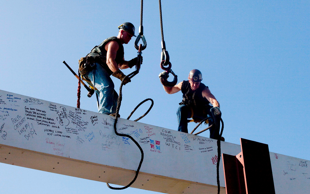 ". In this file photo of Aug. 2, 2012, ironworkers James Brady, left, and Billy Geoghan release the cables from a steel beam after connecting it on the 104th floor of One World Trade Center in New York. The beam was signed by President Barack Obama with the notes: ""We remember,\"" \'\'We rebuild\"" and \""We come back stronger!\"" during a ceremony at the construction site June 14. Also adorned with the autographs of workers and police officers at the site, the beam will be sealed into the structure of the tower, which is scheduled for completion in 2014. (AP Photo/Mark Lennihan, File)"