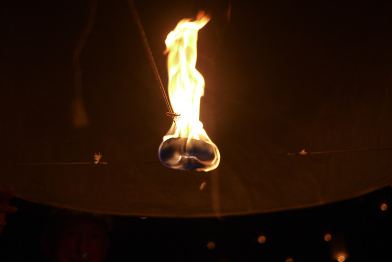 A single flame fills the lanterns with the hot air they need to float away during Loy Krathong in Chiang Mai, Thailand