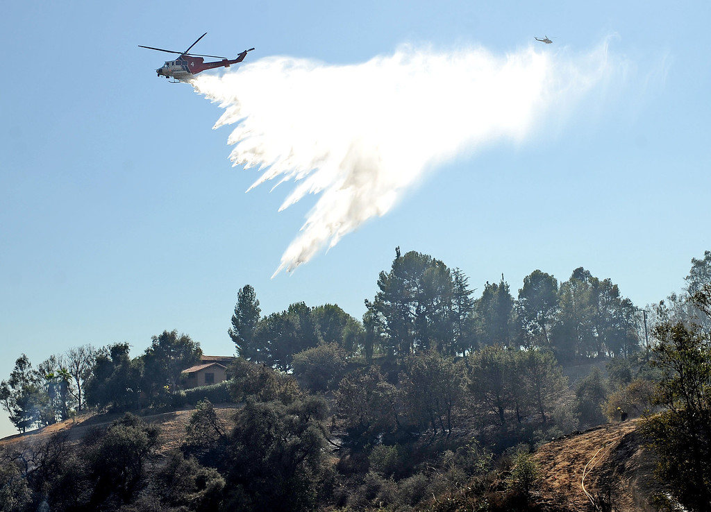 . A helicopter makes a water drop over a home in La Verne Friday during the Canyon Fire. Approximately 27 acres burned in a rugged area in the northern parts of La Verne Friday September 13, 2013. Some homes were evacuated north of Baseline Avenue but no homes were reported damaged. (Will Lester/Inland Valley Daily Bulletin)