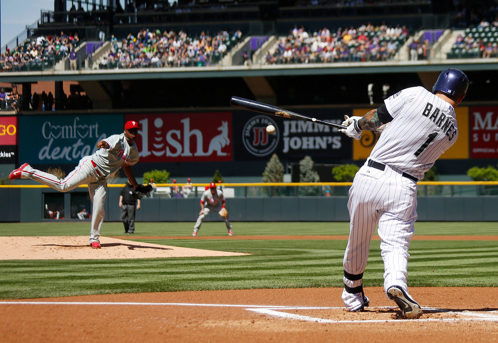 . Colorado Rockies\' Brandon Barnes, foreground, singles off Philadelphia Phillies starting pitcher Roberto Hernandez, left, in the first inning of a baseball game in Denver, Sunday, April 20, 2014. (AP Photo/David Zalubowski)