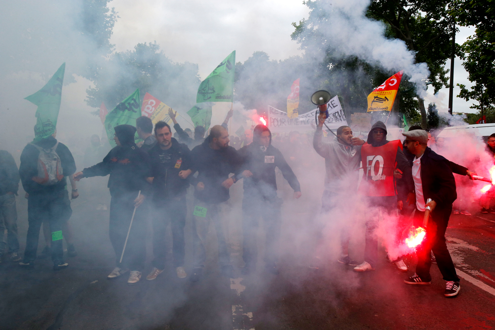 Description of . Striking train workers make a chain as they face French riot police during a protest over a bill to reform the state-run railway system in Paris, Tuesday, June 17, 2014. A weeklong strike by rail workers has caused one of the worst disruptions to the country's rail network in years and is heating up as the reform bill goes to the lower house of Parliament for debate Tuesday. (AP Photo/Michel Euler)
