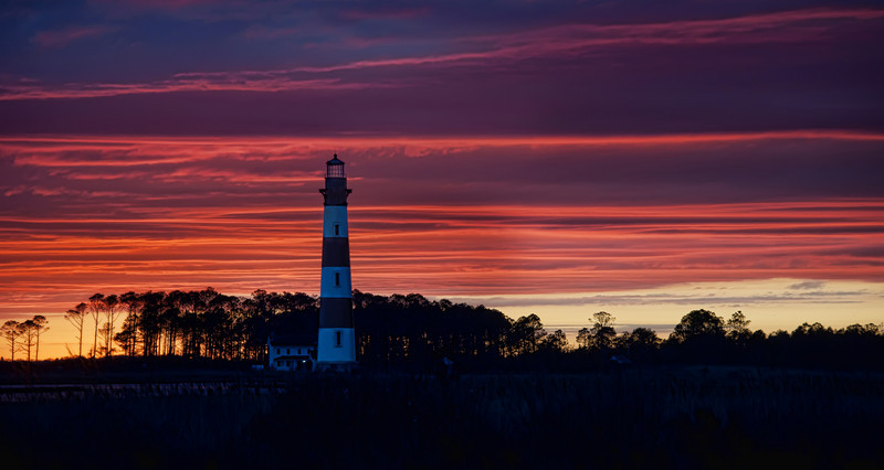 Roanoke Island Lighthouse I'm visiting family for Thanksgiving here on Roanoke Island, and I went out last night after a storm to take some photos. This area is known for beautiful lighthouses, so I put myself on a little mission.I didn't initially plan on going out to take photos. It started with a jog on the beach a bit before sunset. I was jogging north, listening to good music, and the sun was on me. But, ahead of me, the clouds were dark and scary, like the ones circling Mordor. One of those surreal scenes unfolded in front of me… maybe you know the kind. The sun lit everything perfectly below the horizon, and above the horizon was heavy and foreboding. It was then that I decided that it would be an interesting night for photos!So I jogged back to the house, got my rig, and headed out. All this while, I was still in shorts and a t-shirt, which were now wet with rain since the clouds had come to cover me up on the way home. I drove to this nearby lighthouse, but there was no good way to get this angle. The trees in front were about eight feet high, and there was no break in them… the only thing I could do is pull my car over (a rented minivan), and climb up on top with my tripod. There are not many things more slippery than the top of a wet minivan! So, I'm sure I looked like quite a fool clambering my way up there… but up there I got.- Trey RatcliffClick here to read the rest of this post at the Stuck in Customs blog.