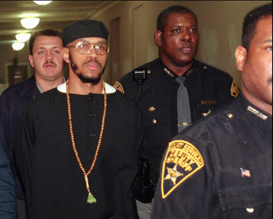 . Carlos Sanders, with cap, is under heavy guard as he is led to court Tuesday, Jan. 16, 1996, in Cincinnati, where jury selection began on his aggravated murder, kidnapping, and assault trial. Sanders is the alleged ringleader in the 1993 Lucasville prison riot. (AP Photo/Al Behrman)