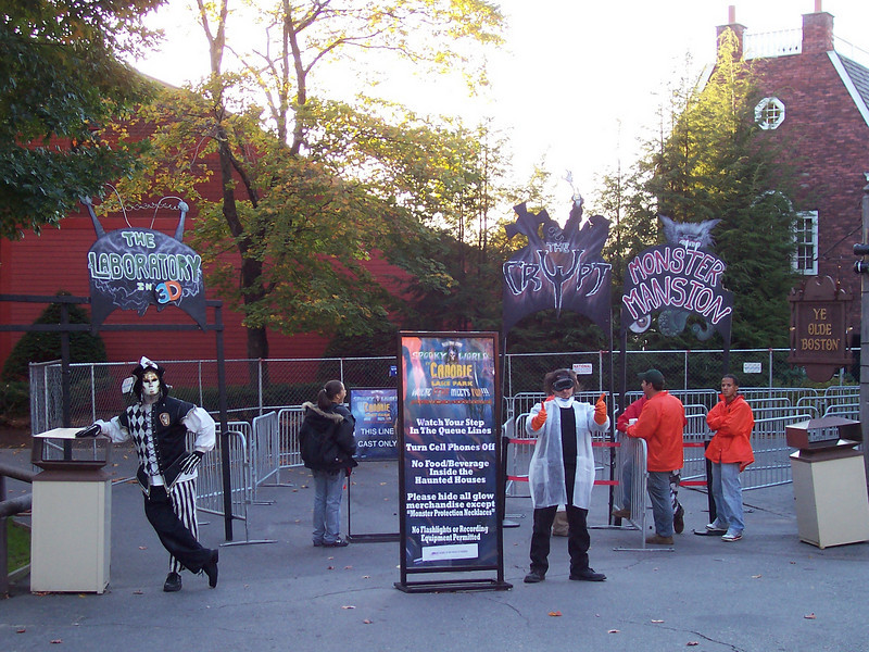 The queue entrances to the haunts, with costumed characters greeting guests.
