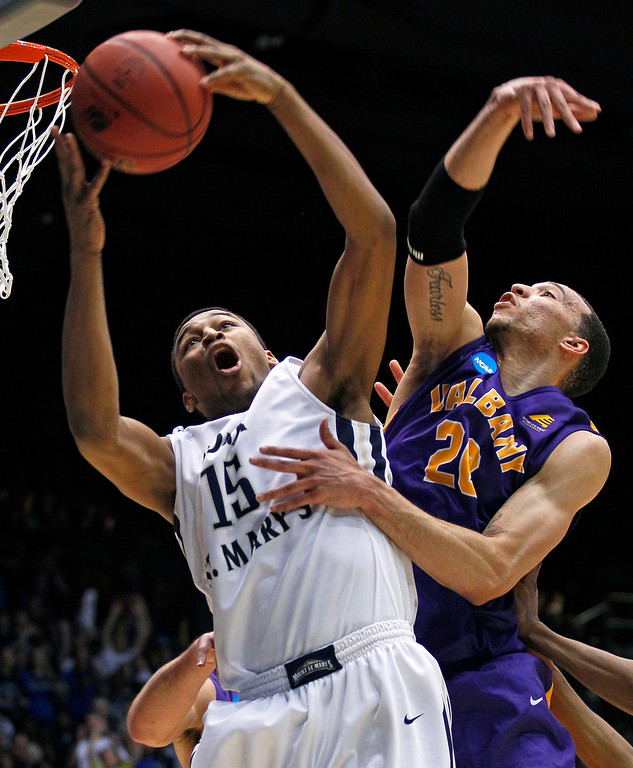 . Mount St. Mary\'s forward Gregory Graves (15) pulls a rebound away from Albany forward Gary Johnson in the first half of a first-round game of the NCAA college basketball tournament, Tuesday, March 18, 2014, in Dayton, Ohio. (AP Photo/Skip Peterson)