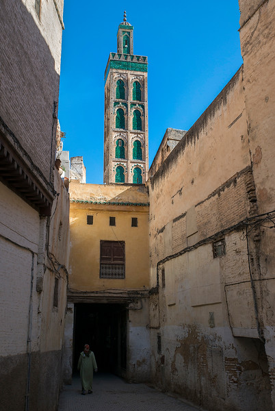 Woman walking along the narrow lanes in the old medina. The minaret of the Sidi Ahmed Tijani mosque can be seen in the background.  Fez, Morocco, 2018